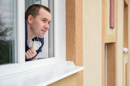 Caucasian adult man smiles, looks out of apartment window and removes the respirator from his face. End of quarantine, self-isolation and the COVID-19 pandemic. Horizontal orientation, copy space.