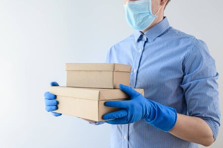 Safe delivery home concept. Courier in protective medical mask and gloves holds cardboard boxes with parcels. Online shopping, stay home, coronavirus pandemic. Horizontal orientation, mockup