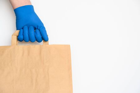 Concept of safe home delivery during coronavirus pandemic. Hand in protective glove holds craft paper bag on white background. Copy space. Zdjęcie Seryjne