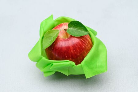 The concept of saving food without plastic. Red apple in a reusable beeswax napkin on a light gray stone background. Zero waste.