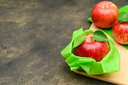 The concept of saving food without plastic. Red apple in a reusable beeswax napkin on rustic background. Copy space. Zero waste.