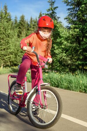 Cute little girl in a protective mask rides a bicycle in a city park. Vertical orientation. Reklamní fotografie