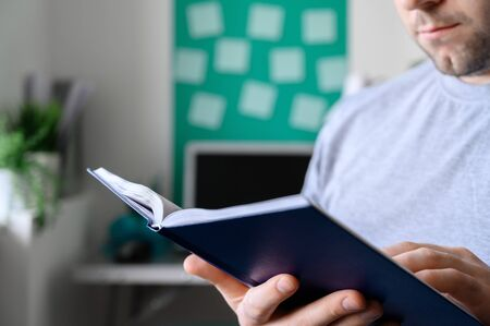 Man takes break from work, sits in his living room and reads book. Part of the body and the book close up. Digital detox concept. Horizontal orientation.