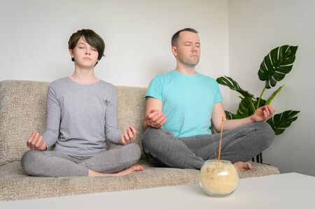 Father and daughter are meditating, sitting in lotus position on the couch. Yoga at home. horizontal orientation. Фото со стока