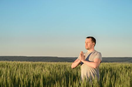 Adult man stands on a field in tall grass doing yoga during sunset. Digital detox, connection with nature concept. Copy space. Stock fotó