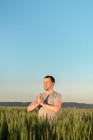 Adult man stands on a field in tall grass doing yoga during sunset. Digital detox, connection with nature concept. Copy space, vertical.