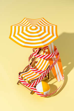 Deck chair, umbrella, surfboard and ball are wound with protective signal tape on the beach. Concept of closed beach. Miniature minimalistic composition. Vertical orientation