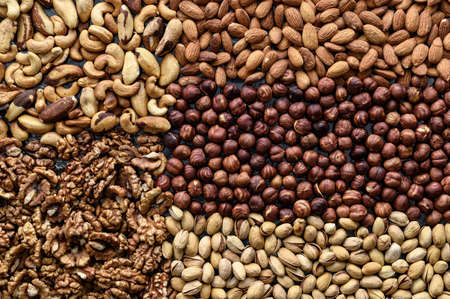 Variety of nuts background. Sources of protein and fat for vegans. Healthy food concept. Top view, horizontal orientation.