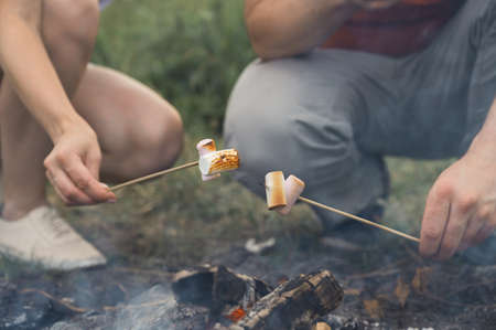 Guy and the girl are frying marshmallows on a campfire. Friends hold sticks with marshmallows over a bonfire. Horizontal orientation, selective focus. Banco de Imagens