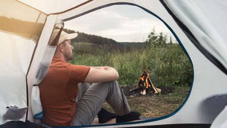 Young man sits near a tent and bonfire against the backdrop of nature. View through the tent. Concept of local travel, tourism and camping. Copy space.