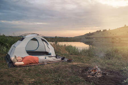 Young man lies on a rug near a tent and a bonfire against the backdrop of nature and the lake. Evening time, dramatic sky. Concept of local travel, tourism and camping. Copy space. Banco de Imagens - 151218298