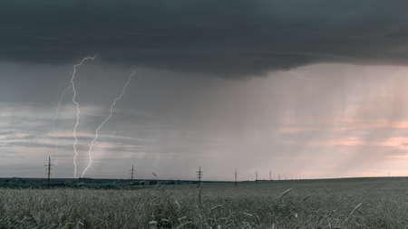 Lightning on a dark gray sky during a storm shower. Dramatic sunset sky. Banco de Imagens - 151618563