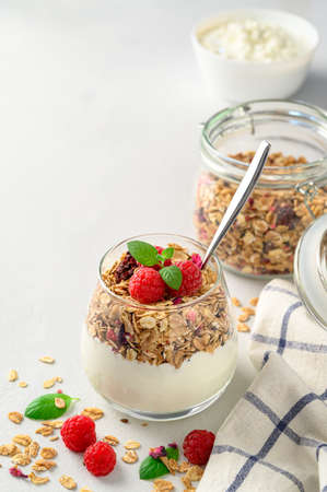 Parfait yogurt with granola and raspberries in a glass, light background, copy space. Healthy breakfast concept. Banco de Imagens - 151575429