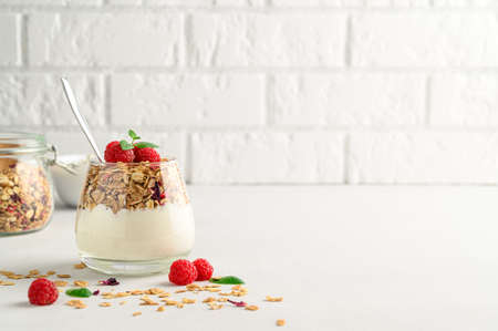 Parfait yogurt with granola and raspberries in a glass, light background, copy space. Healthy breakfast concept.