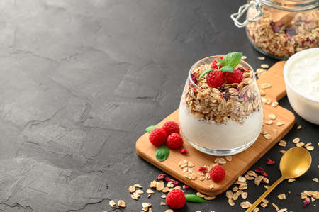 Parfait yogurt with granola and raspberries in a glass, black background, copy space. Healthy breakfast concept. Banco de Imagens - 151618566