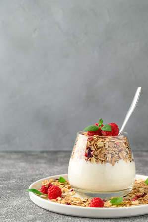 Parfait yogurt with granola and raspberries in a glass, gray stone background, copy space. Healthy breakfast concept. Banco de Imagens - 151577177