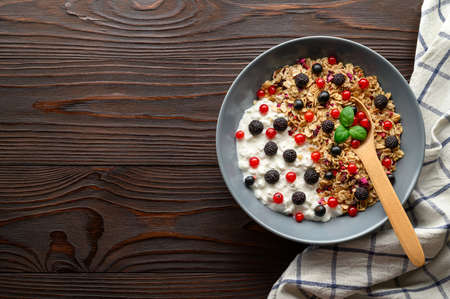Healthy breakfast. Bowl with oat granola, yogurt and black raspberries, black and red currants on a brown wooden background. Top view, copy space.