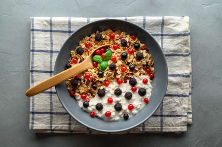 Healthy breakfast. Bowl with oat granola, yogurt and black raspberries, black and red currants on a gray concrete background. Top view.