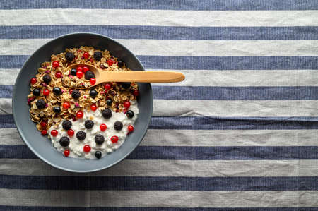 Healthy breakfast concept. A bowl with oat granola, yogurt and black raspberries, black and red currants on a striped textile napkin. Top view, copy space.