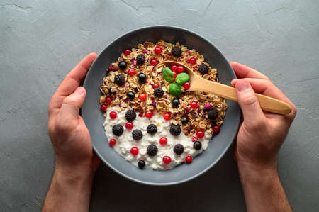 Healthy breakfast concept. Male hands are holding a wooden spoon and a bowl with oat granola, yogurt and black raspberries, black and red currants. Gray concrete background. Top view. Banco de Imagens