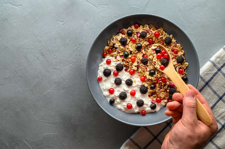 Healthy breakfast concept. A mans hand holds a wooden spoon over a bowl with oat granola, yogurt and black raspberries, black and red currants. Gray concrete background. Top view, copy space.