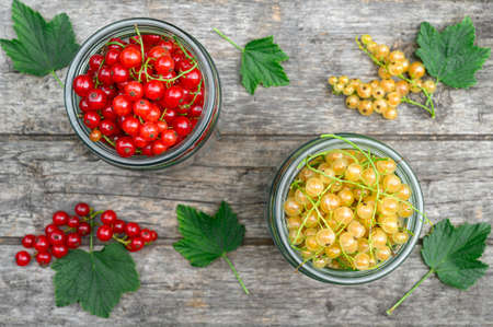 Red and white currants in glass jars. Eco food concept. Top view. Banco de Imagens