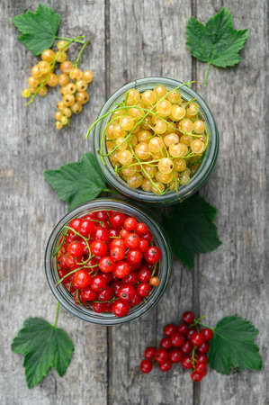 Red and white currants in glass jars. Eco food concept. Top view, vertical orientation.