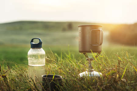 Camping gas burner outdoors on a sunset background. Cooking food during the hike. Adventure, travel, tourism and camping concept.
