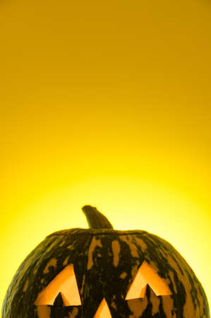Happy Halloween. Crop funny glowing pumpkin Jack-o-lantern on a yellow background. Place for text, vertical orientation.