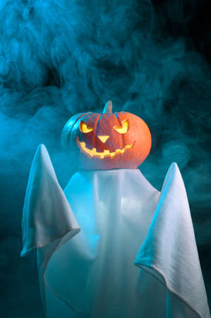 Halloween concept. A ghost with a creepy head glowing jack-o-lantern pumpkin stands in the fog at dusk. Vertical orientation, copy space