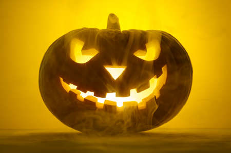Happy Halloween. Scary glowing pumpkin Jack-o-lantern in the smoke on a yellow background. Selective focus