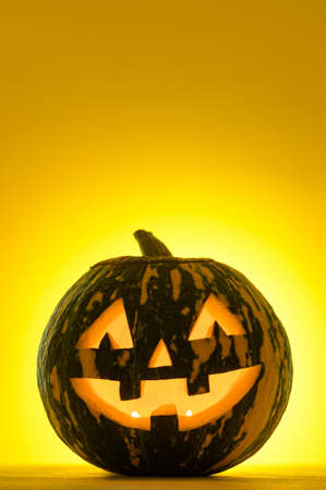 Happy Halloween. Funny glowing pumpkin Jack-o-lantern on a yellow background. Copy space, vertical orientation. Selective focus
