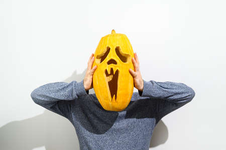 Anonymous Man in a sweater holds a carved Halloween pumpkin in front of his face on a white background. Faceless concept. Copy space