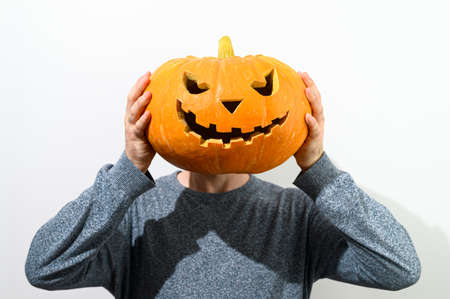 Anonymous Man in a blue sweater holds a carved Halloween pumpkin in front of self-face on a white background. Faceless concept. Crop portrait.