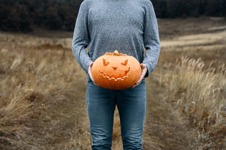 Anonymous Man in blue wear holds a carved orange Halloween pumpkin in front of him, outdoors. Copy space, crop body. Daytime 스톡 콘텐츠