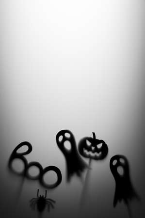 Halloween Decoration. Terrifying Shadow Puppets. Shadows pumpkin, ghost, spider, and Boo word on the gray background. Copy space vertical orientation.