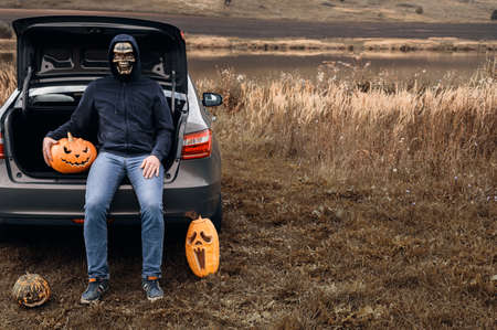 An unrecognizable adult man wearing a skull mask sits in the trunk of a car with carved pumpkins for Halloween, outdoors. Trick or trunk. Copy space.