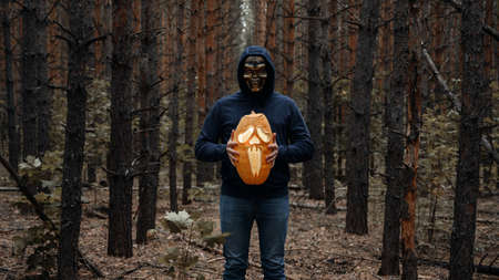 Halloween holiday. A man in a skull mask holds in front of him a glowing Halloween pumpkin in a dark forest. Faceless. Horror and fear concept.