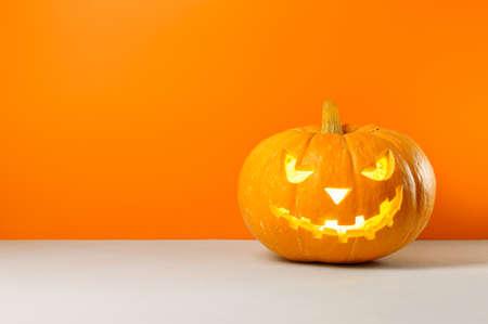 Glowing Halloween pumpkin on a orange background. Copy space.