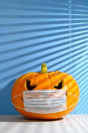 New normal concept. Glowing Halloween pumpkin in a protective medical mask on a pastel blue background, illuminated by sunlight through the jalousie. Space for text, vertical orientation