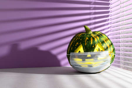 New normal concept. Funny smiling Halloween pumpkin in a protective medical mask on a purple background, illuminated by sunlight through the jalousie. Halloween symbol 2020, Copy space