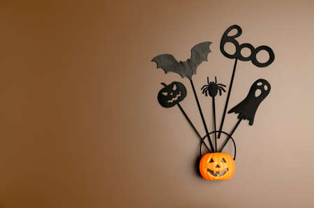 Halloween background. Top view Halloween party accessories and Jack-O-lantern pumpkin on pastel brown background. Flat lay, place for text. Minimal style.