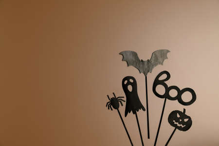 Happy Halloween day. Top view Halloween party accessories on pastel brown background. Flat lay, copy space. Minimal style. Banco de Imagens