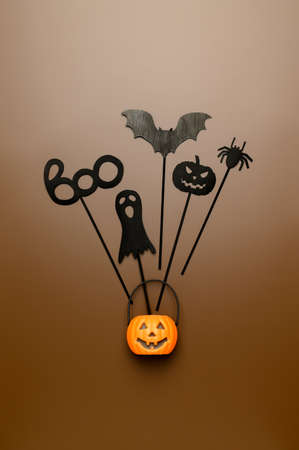 Halloween decoration. Top view Halloween party accessories and Jack-O-lantern pumpkin on pastel brown background. Flat lay, place for text. Minimal style. Vertical orientation