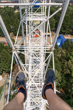 From above anonymous man in sneakers riding modern Ferris wheel over green trees on fairground in summer