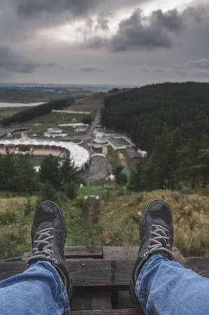 Unrecognizable person in jeans and sneakers sitting on wooden structure on hill near town and resting on overcast day