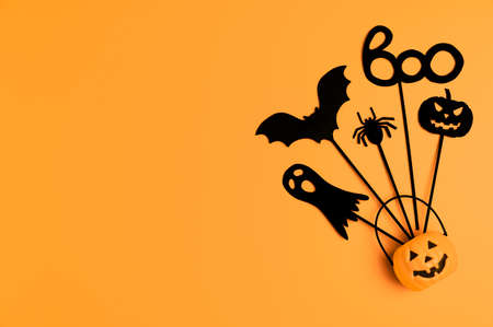 Halloween background. Top view Halloween party accessories and Jack-O-lantern pumpkin on orange background. Flat lay, place for text. Minimal style. Banco de Imagens