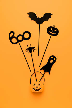 Halloween decoration. Top view Halloween party accessories and Jack-O-lantern pumpkin on orange background. Flat lay, place for text. Minimal style. Vertical orientation Banco de Imagens