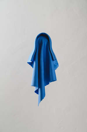 Flying Halloween Ghost. Scary blue ghost on light gray background. Vertical orientation