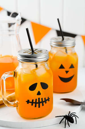 Halloween pumpkin iced mocktails in glass jars decorated with scary faces on a white table. DIY Halloween Party decoration on the wall. Party cocktails. Vertical orientation